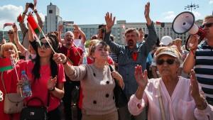 """Сторонники главы государства принесли с собой белорусские флаги и плакаты с надписями """"Сохраним Беларусь""""."""