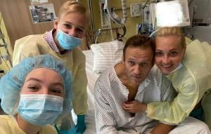 На фото из больничной палаты он находится в окружении своей семьи.