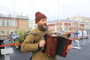 """Невозможно было пройти мимо музыкальной площадки, где один из артистов самарского фольклорного ансамбля """"Карагод"""" в образе партизана пел под гармонь военные песни."""