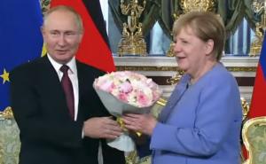 Перед началом переговоров в Кремле российский лидер преподнес Меркель букет цветов.
