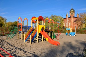 Для безопасности малышей детская площадка имеет песчаное покрытие и ограждение.